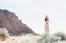 Young woman wearing long white dress standing in prairie with arms raised. — Stock Photo