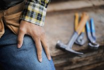 Cropped view of man sitting at workbench with grippers and pliers lined up on plank of wood. — Stock Photo