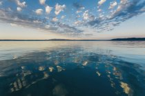Dramatic clouds reflecting in calm ocean at dusk at Puget Sound, Washington — Stock Photo