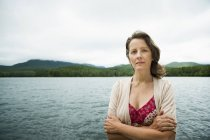 Mature woman in open countryside standing with arms folded by mountain lake. — Stock Photo