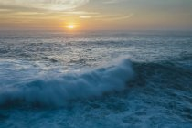 Sunset over horizon over crashing waves and surf. — Stock Photo