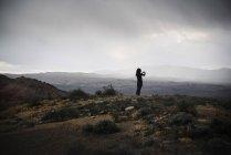 Жінка, стоячи в прерії під хмарного неба і беручи картинка з смартфона — стокове фото