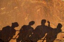 Ombre di persone che si appoggia sulla ringhiera sulla superficie della roccia di Twyfelfontein in Namibia — Foto stock