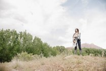 Young woman with long brown hair standing in prairie under cloudy sky. — Stock Photo