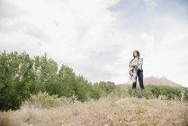 Молода жінка з довге каштанове волосся стоячи в прерії під хмарного неба — стокове фото