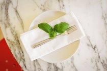 Tovagliolo e piano in marmo con foglie di basilico e forchetta . — Foto stock
