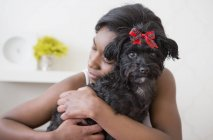 Девочка-подросток обнимает маленькую черную собаку с красным бантом . — стоковое фото