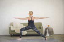Blonde woman standing on yoga mat with legs apart and arms outstretched. — Stock Photo