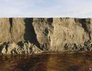 Eroding sand cliff and moving water along intertidal area. — Stock Photo