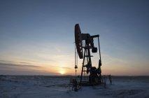 Appareil de forage pétrolier et cric de pompage dans une plaine plate du champ pétrolifère canadien au coucher du soleil . — Photo de stock