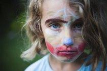 Mädchen im Grundalter mit einem Gesicht, das mit Farben verziert ist. — Stockfoto