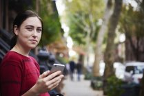 Young woman standing on city street, holding smartphone and looking in camera. — Stock Photo