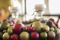 Close-up of colorful Christmas ornaments and candles in candle holder on table. — Stock Photo