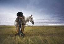 Cowboy leaning on fence post with grey horse behind in countryside. — Stock Photo