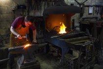 Weiblichen Schmied auffällig rote Roheisen auf Amboss in Werkstatt — Stockfoto