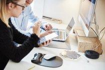 Deux personnes travaillent ensemble sur tablette, ordinateur portable et moniteur . — Photo de stock