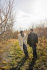 Young couple holding hands while walking in orchard in winter. — Stock Photo