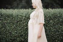 Vista lateral da mulher grávida em vestido branco em pé no jardim verde . — Fotografia de Stock