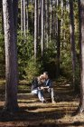 Woman leaning on male shoulder while sitting on log in pine forest. — Stock Photo