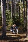 Mulher se apoiando no ombro masculino enquanto sentado em log na floresta de pinheiros . — Fotografia de Stock