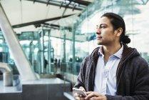 Середині дорослий чоловік тримає мобільного телефону, поки стоїть місто доріжки — стокове фото