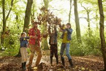 Family throwing dried leaves into air in woods in autumn. — Stock Photo