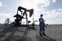 Homme en salopette et casque au cric de la pompe en pleine terre sur le site d'extraction d'huile . — Photo de stock