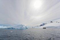 Група людей в гумовому човні поблизу айсберг офшорних в Антарктиці. — стокове фото