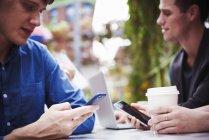 Jeunes hommes assis à table en ville et travaillant avec un ordinateur portable et des téléphones . — Photo de stock