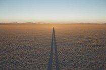 Тень человека на черном рок пустыни Playa в сумерках, Невада, США — стоковое фото