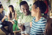 Couple drinking from wine glasses with group of friends at house party. — Stock Photo