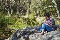Woman sitting on rocks by river and using smartphone. — Stock Photo