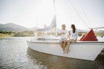 Hombre y la mujer sentada en velero con adolescentes en fondo. - foto de stock