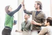 Коллеги смеются и делятся своим жестом во время кофе-брейка . — стоковое фото