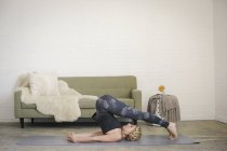 Blonde woman lying on yoga mat and bending down over head. — Stock Photo