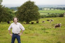 Man standing with hands on hips in meadow with grazing herd of English Longhorn cattle. — Stock Photo