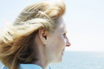 Profile of blonde mature woman standing by ocean. — Stock Photo