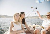 Pareja madura y rubia hija adolescente relajante en velero. - foto de stock