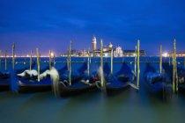 Гондолы лодки пришвартованы на берегу с видом на остров и церковь Сан-Джорджо Маджоре в сумерках, Венеция, Италия. — стоковое фото
