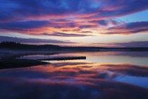 Muelle de madera en lago tranquilo al atardecer con paisaje nublado dramático . - foto de stock