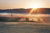 Glowing dawn sunlight on golf course with pole. — Stock Photo