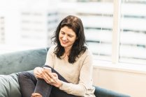 Женщина, сидящая с ноги на диване, улыбаясь и с помощью смартфона — стоковое фото