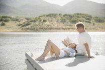 Man and woman reclining on jetty and reading book. — Stock Photo