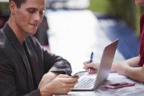 Hombre joven sentado en la mesa al aire libre con la mujer y portátil abierto y mirando hacia abajo en el teléfono inteligente . - foto de stock