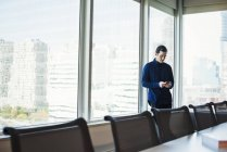 Jeune homme debout à côté de la table dans la salle de réunion et en regardant de smartphone. — Photo de stock