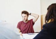 Молодой человек сидит на встрече с коллегами за столом . — стоковое фото