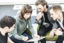 Colleghi a riunione che scrivono con penna su appunti . — Foto stock