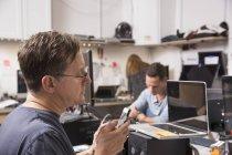 Зрілі чоловік дивиться на телефон в інтер'єрі лабораторії технології. — стокове фото