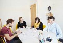 Mitarbeiter bei Geschäftstreffen Tisch ausgebreitet mit Papieren, Männer mit Tablet-PC und laptop — Stockfoto