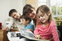 Two parents and children reading together at home. — Stockfoto